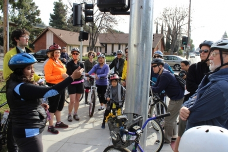Tour attendes listen to Valeria Craven, left, as she describes the danger crossing the Escuela and California Intersection. Photo By Daniel DeBolt, Mountain View Voice.